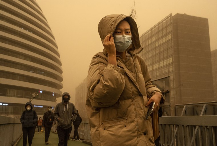 A woman commutes during a sandstorm on March 15, 2021 in Beijing.
