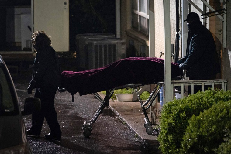 A body is carried out on a stretcher from a spa where three people were shot and killed on March 16, 2021, in Atlanta.