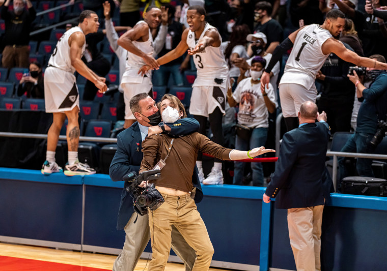 Image: A cameraman from the St. Bonaventure University athletic department is restrained by a security guard at UD Arena during A-10 tournament title basketball game in Dayton