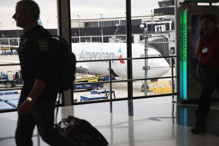 An American Airlines aricraft sits at a gate.