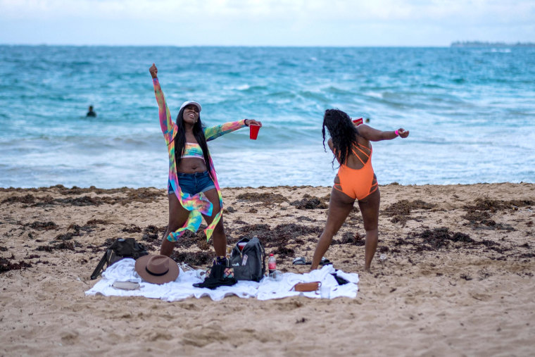 Image: A couple of tourists dance in the beach in the tourist zone of El Condado in San Juan, Puerto Rico on March 14, 2021.