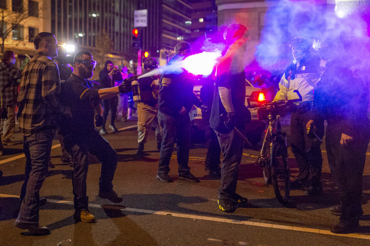 A member of the Proud Boys sprays a police officer with a chemical agent in downtown Washington as the group clashed continuously with counter-protesters on the evening of the second Million MAGA March in on Dec. 12, 2020.