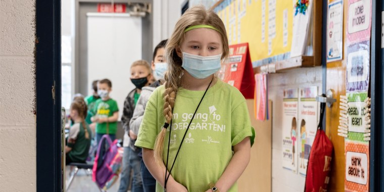 Image: Masked students wait in a socially distanced single file line before heading to the cafeteria at Medora Elementary School on March 17, 2021 in Louisville, Kentucky. Today marks the reopening of Jefferson County Public Schools for in-person learning