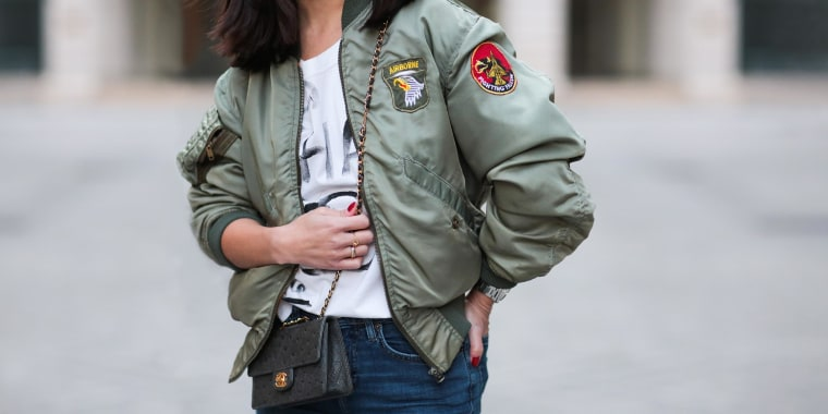 Woman posing wearing a army green bomber jacket