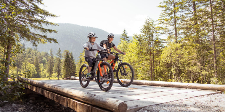 Mother and daughter riding bikes with helmets, through a scenic outdoor path