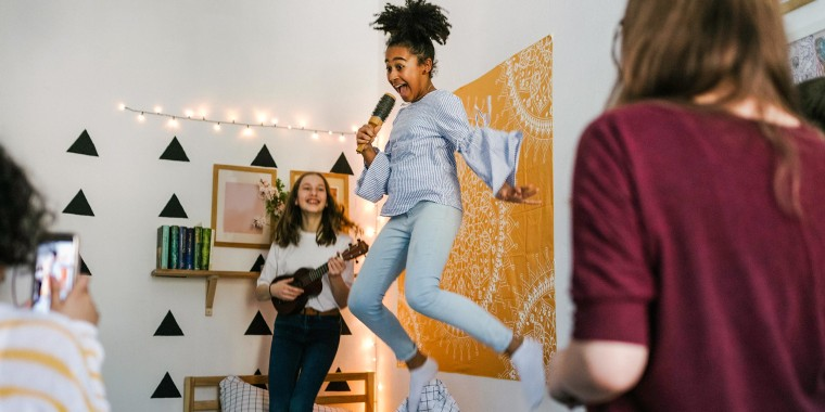 Girl in her bedroom, jumping on her bed, holding a brush pretending to sing, surrounded by three friends