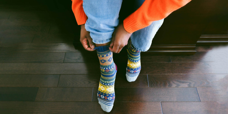 Woman putting on colorful, bright, multi-color socks, she got as a gift