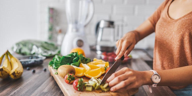 Woman in the kitchen chopping fruits on her wooden cutting board