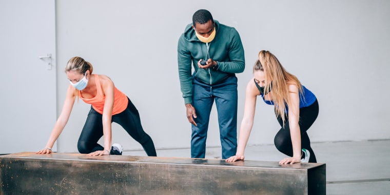 Trainer wearing a double mask working with his clients, also wearing masks. Looking for a face mask to workout in? Shop the best exercise face masks of 2021 according to doctors and trainers from Lululemon, Under Armour and more.