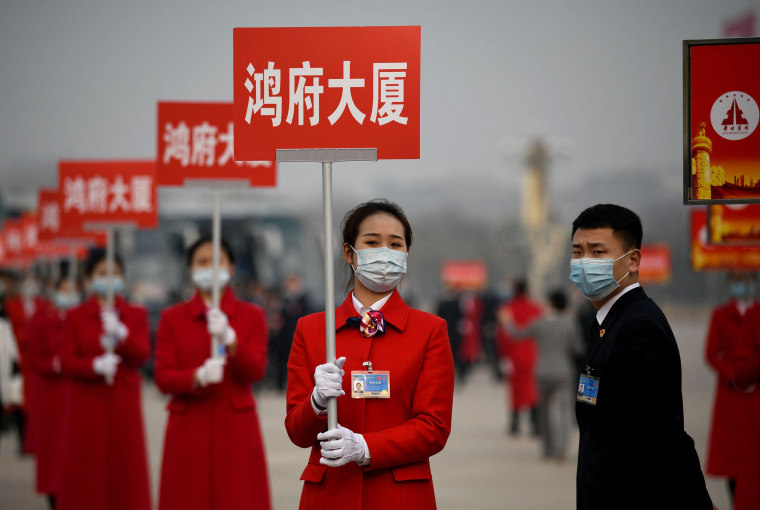 Image: Attendants wait in Tiananmen Square to lead delegates back to their buses after the closing session of the Chinese People's Political Consultative Conference in Beijing