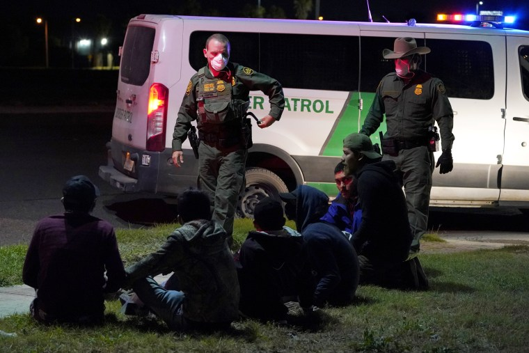 U.S. Customs and Border Protection agents take people into custody people near the border with Mexico on March 20, 2021, in Hidalgo, Texas.