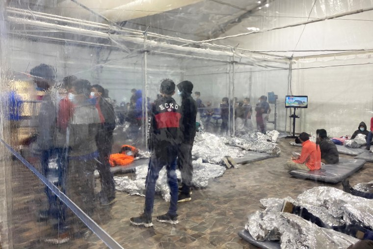 Migrants crowd a room with walls of plastic sheeting at the U.S. Customs and Border Protection temporary processing center in Donna, Texas, in a recent photograph released March 22, 2021.
