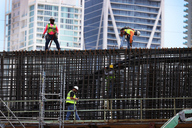 """Construction workers build the \""""Signature Bridge\"""" in Miami on March 17, 2021."""