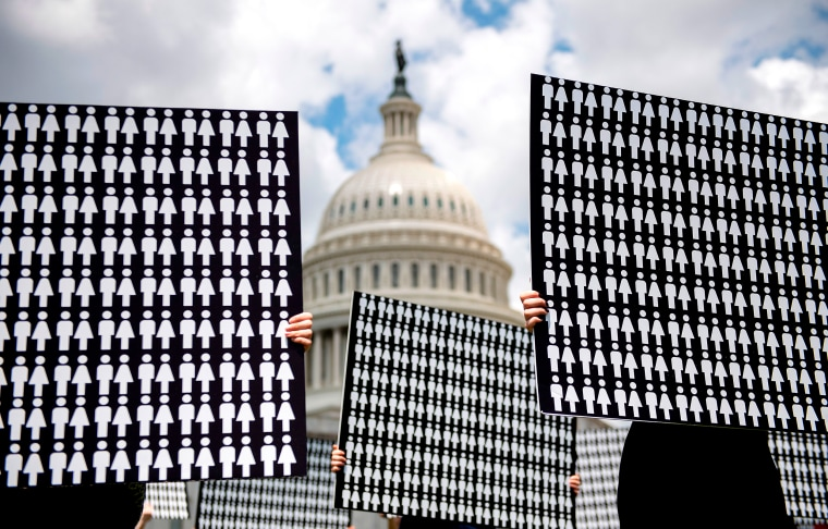 Image: Hands holding up placards representing people against the Capitol Hill in the background.