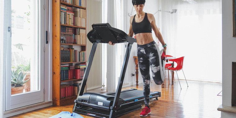 Woman in her house, stretching next to her treadmill