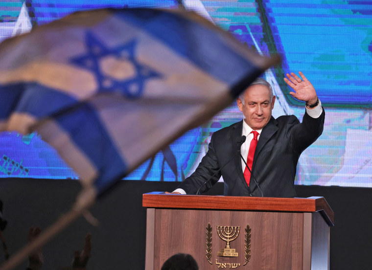 Image: Israeli Prime Minister Benjamin Netanyahu, leader of the Likud party, waves to supporters at the party campaign headquarters in Jerusalem