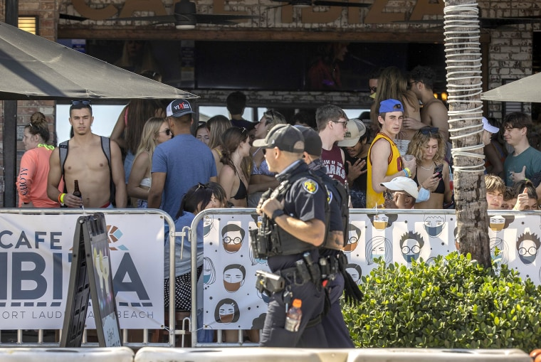 Image: Fort Lauderdale police officers walk past people enjoying themselves at Cafe Ibiza on March 4, 2021 in Fort Lauderdale, Fla.