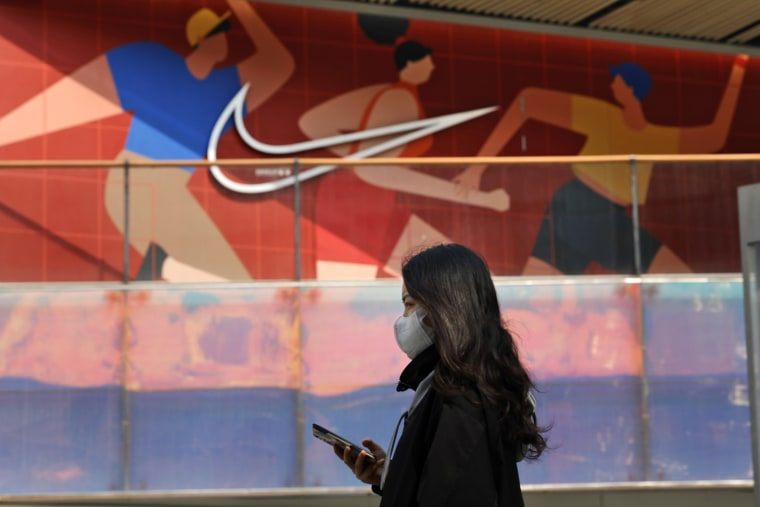 Image: A woman wearing a mask passes by a Nike store in Beijing