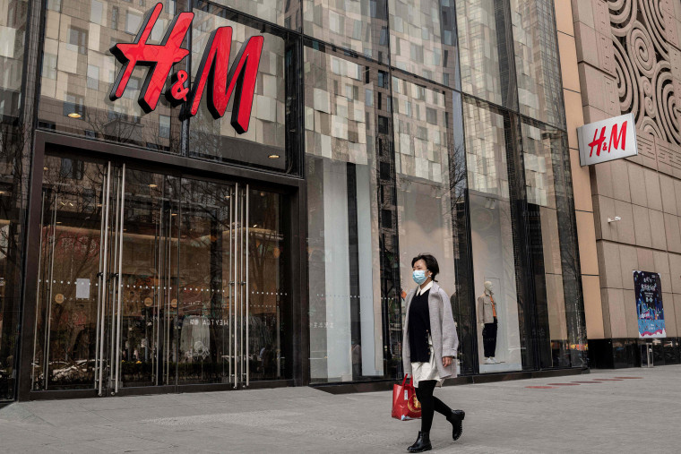 Image: A woman walks past a store of Swedish clothing giant H&M in Beijing