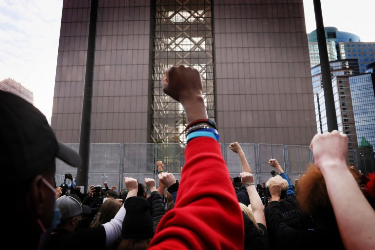 People raise their fists in front of the Hennepin County Courthouse in Minneapolis, Minn. on March 7, 2021.