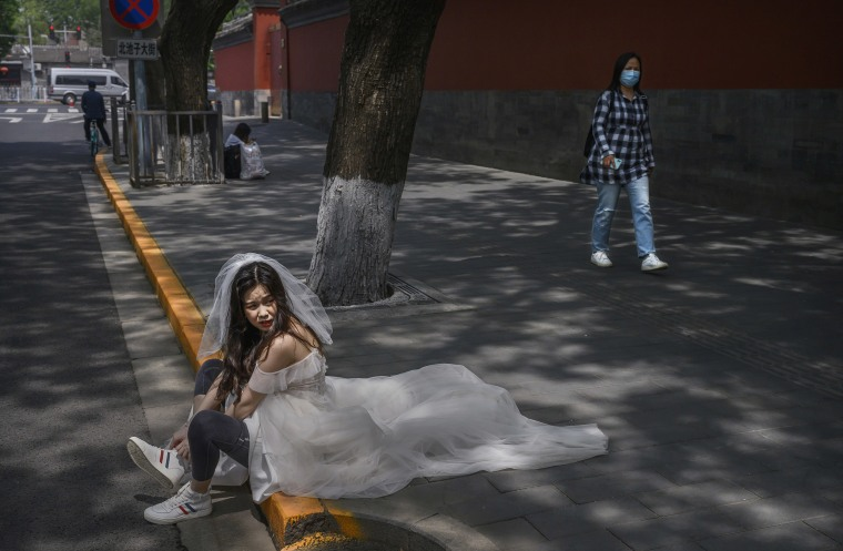 Image: A Chinese woman puts on her sneakers after taking pictures in advance of her wedding near the Forbidden City
