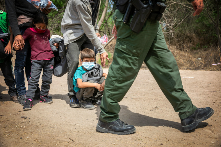 Asylum seekers await transport by U.S. Border Patrol agents on March 25, 2021 in Hidalgo, Texas.