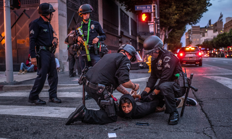 Image: Two police officers detain and handcuff a person on the street and two police officers stand by.