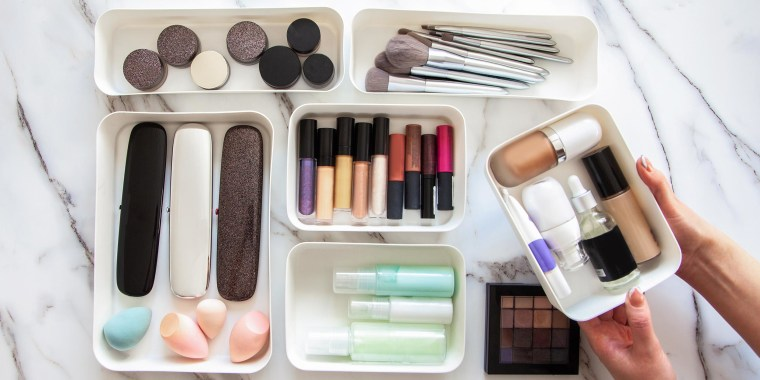 Overhead image of a Woman organizing her makeup, brushes and beauty items, in white storage containers