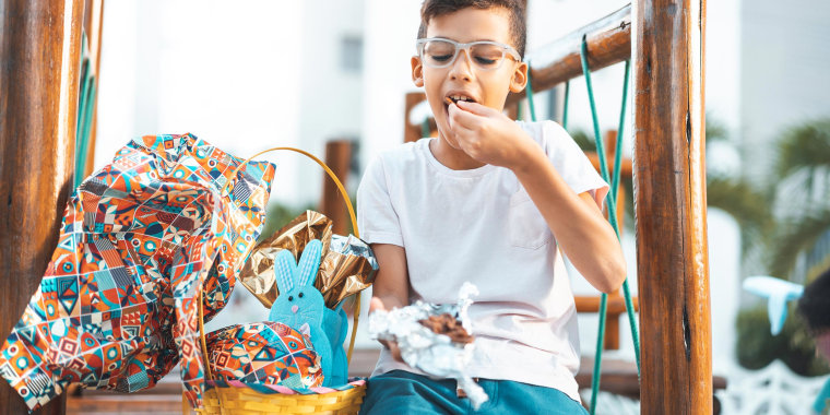 Little boy with glasses, eating chocolate out of a packaged Easter Basket