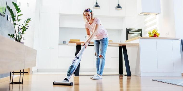 Woman in her kitchen vacuuming her wooden floor