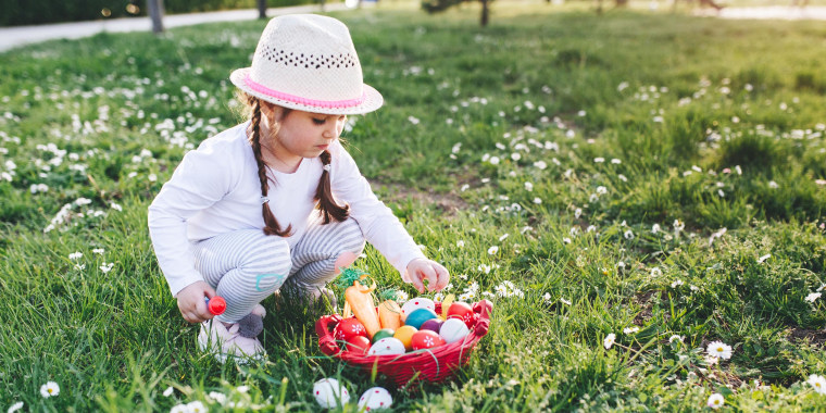 Little girl crouching outside, looking at her stuffed Easter basket