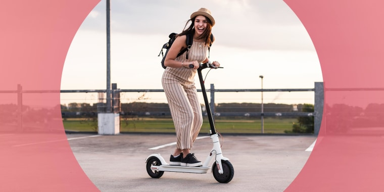Woman in a jumpsuit and a hat, riding her white electric scooter