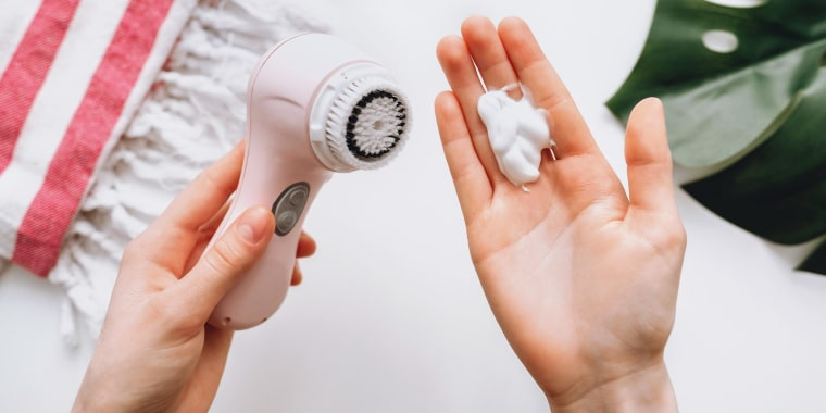 Image of a Woman holding a pink facial cleansing brush in one hand and soap in the other hand