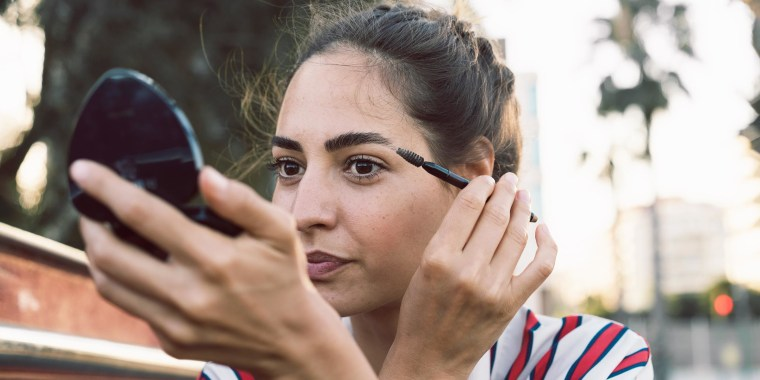 Woman looking into compact mirror brushing her brows