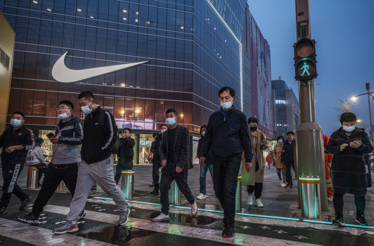 Image: People cross a street in front of a Nike store at a shopping area on March 26, 2021 in Beijing, China.