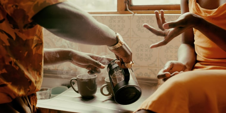 Close up image of a man and woman in a kitchen, pouring two cups of steaming coffee, from a French Press