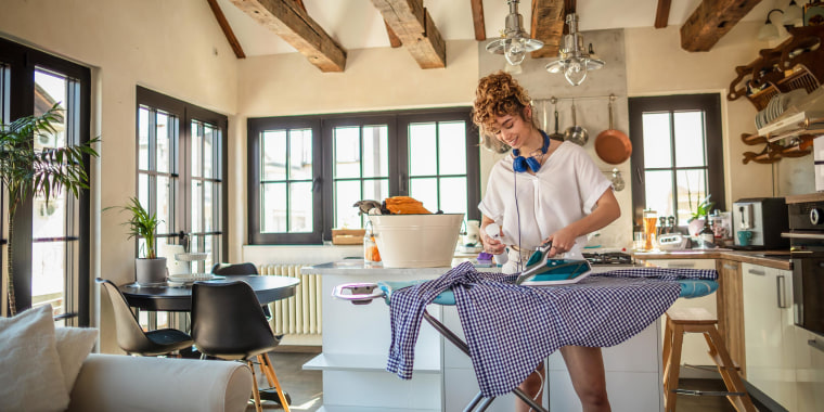Woman wearing a white t-shirt and headphones, ironing and steaming a checkered blue shirt in her kitchen. These are the 6 best irons to get wrinkle free clothes in 2021. Shop the best steam irons from Black & Decker, Maytag, Hamilton Beach and more.