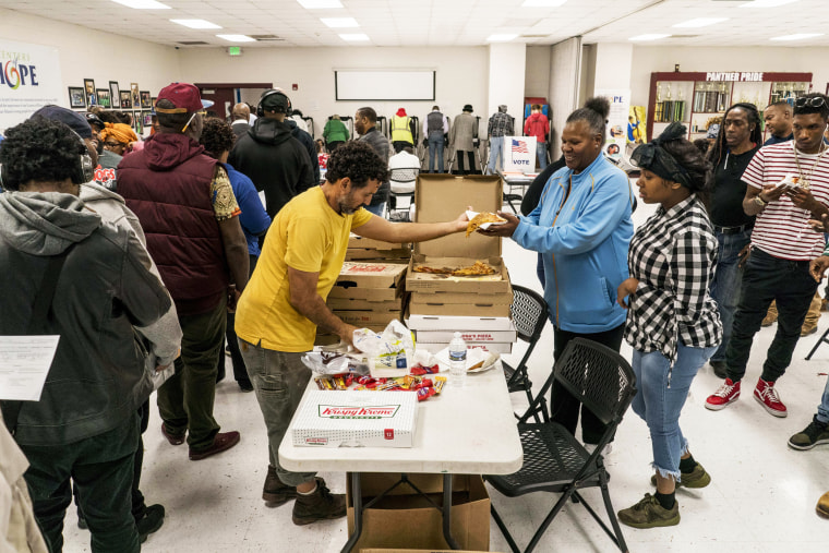 Voters enjoy pizza while they wait in line to vote in Atlanta on Nov. 6, 2018.