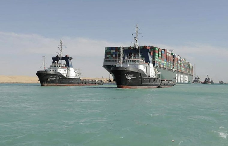 Image: A tugboat pulling the Panama-flagged MV 'Ever Given' container ship after it was fully dislodged from the banks of the Suez