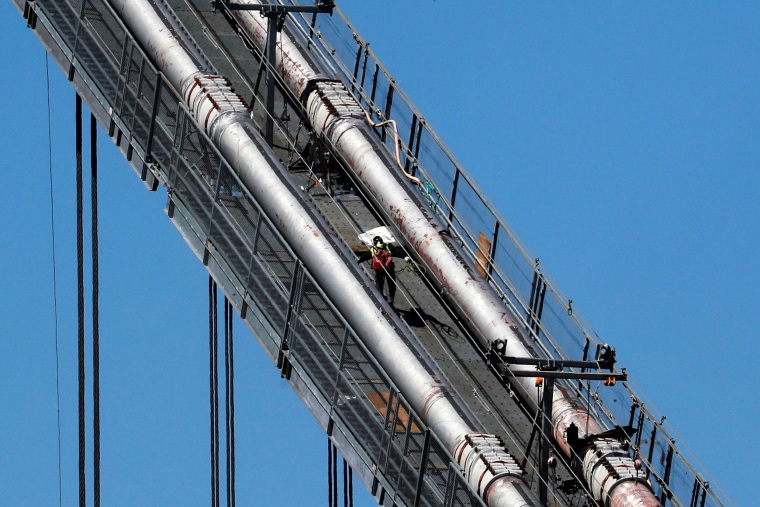 Image: A construction worker scales the northeast cables of the George Washington Bridge duering reconstruction in New York