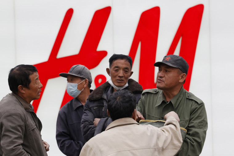 Image: Migrant workers gather near an H&M store in Beijing