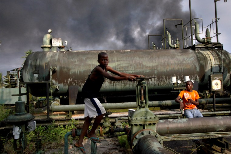 Image: Children play on an abandoned oil flow station near smoke from a burning oil pipe in Kegbara-Dere, Nigeria, in 2007.