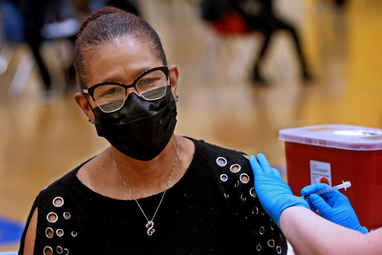 Image: Janette Davis gets a Covd-19 vaccine at North Division High School in Milwaukee on March 22, 2021.