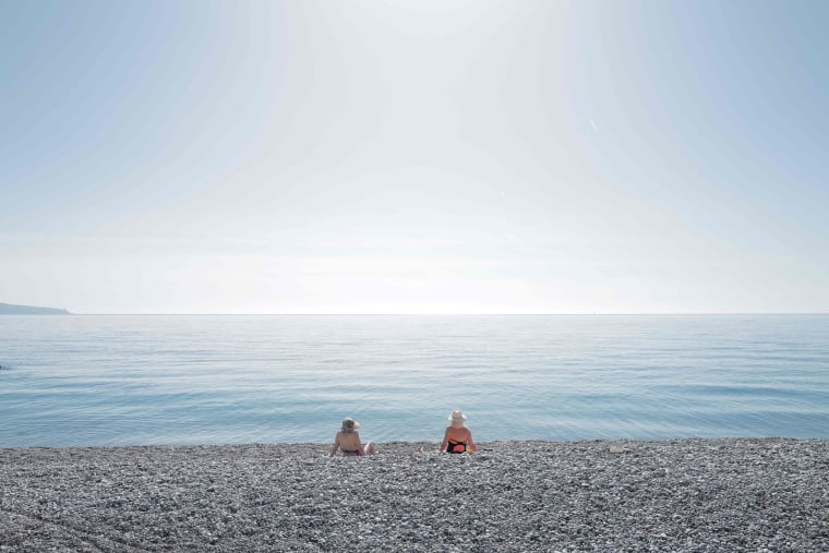 Image: Two women sit on the beach