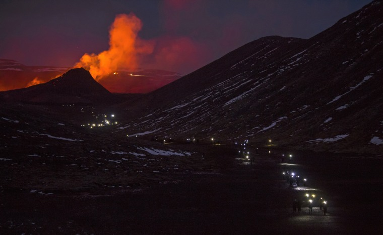 Image: People use flashlights as they take the pathway down after watching the lava flows