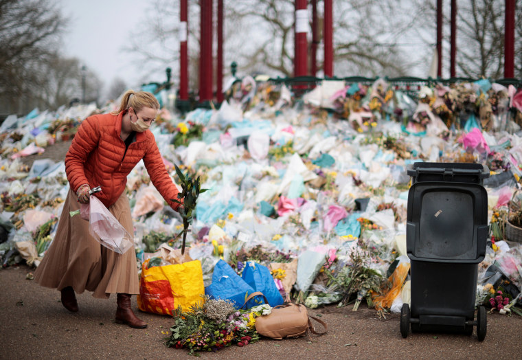 Image: Clapham Women's Institute members clear floral tributes from a memorial to Sarah Everard, in London