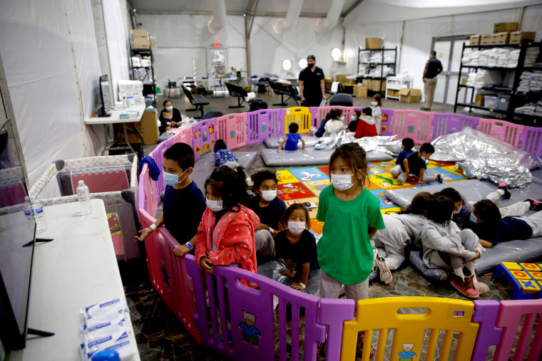 Image: Young unaccompanied migrants, ages 3-9 watch TV inside a playpen at the Donna Department of Homeland Security holding facility