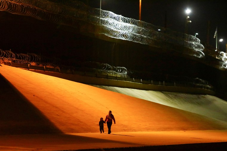Image: A mother and her son, migrants from Honduras, walk after crossing the Rio Bravo river to turn themselves in to U.S Border Patrol agents to request for asylum in El Paso, Texas, U.S., as seen from Ciudad Juarez