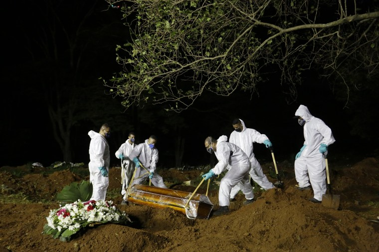 Image: Cemetery workers lower the coffin of a COVID-19 victim