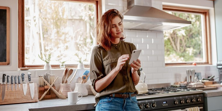 Woman standing in her kitchen looking at her phone screen